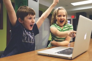 Two children sit in front of a laptop computer. the boy has his arms raised in triumph. The girl points and looks amazed.