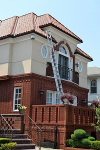 A long ladder is resting against the gutter of a two storey house