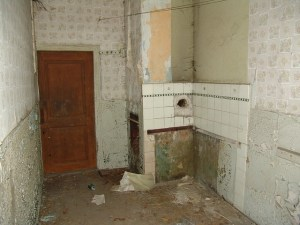 Bathroom in an old house has been stripped and bare walls and old tiles remain