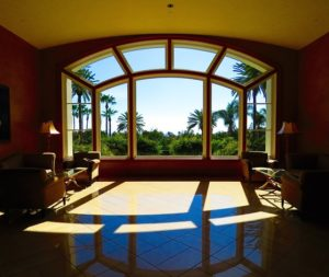 A large arched window lets in light. It has struts that cast line shadows over the floor