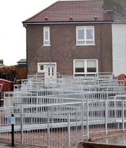 A suburban house in UK. The ramp makes several zig-zags up the front of the house. It looks ugly.