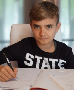 A boy sits at a desk, pen in hand ready to write on the paper.