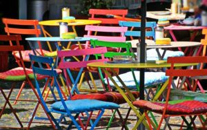 brightly coloured simple folding chairs in an outdoor cafe setting.