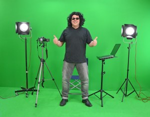 A man stands against a greenbox bacground with lights and cameras around him