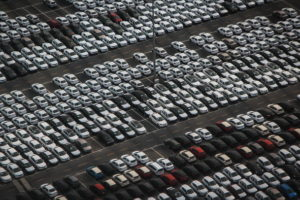An aerial view of a car manufacturer's parking lot showing rows of white cars