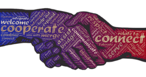 Graphic of a handshake with purple hands. The hands have words on them such as cooperate and connect
