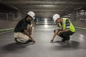 Two men in hard hats are crouching on a large concrete floor.they look like they are discussing something.