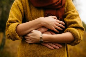 A woman wearing a mustard coloured jumper is hold the the hands of someone who is hugging her from behind. There is no head, just the torso.