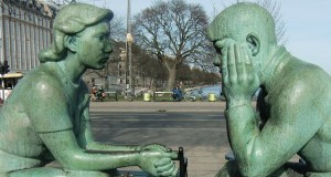 Two green statues, one a man the other a woman sit facing each other in a gesture of communicating with each other.