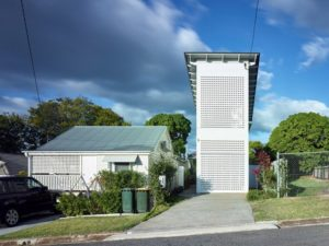 Picture of a tall long skinny house with white lattice covering. It fits into a driveway.