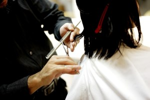 A woman with dark hair is getting a haircut from a hairdresser
