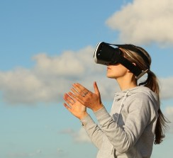 A young woman is wearing a pair of virtual reality goggles and looking towards the sky.
