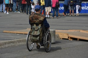 A man in a wheelchair is separated from the crowd by a low concrete barrier