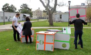 A group of students are on the grass outside the university building. they have several large cardboard shapes and appear to be arranging them in some kind of format.