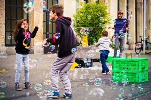 Children play with bubbles in urban area.