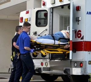 Two ambulance officers push a patient into the ambulance.