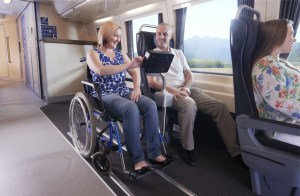 In the train carriage, a woman is seated in a manual wheelchair and is sitting next to a man in a standard seat. They are looking at an in-seat screen, probably for movies.