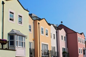 A row of two storey houses painted in different pastel colours.