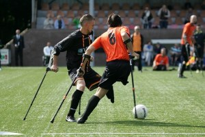 Two young men each with one leg and using crutches, compete for the football on the football field. Kicking UD Goals in Sport.