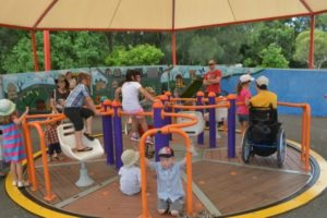 children and adults are on a spinner. Some children are siting and one person is in a wheelchair. There are three seats on the spinner as well.