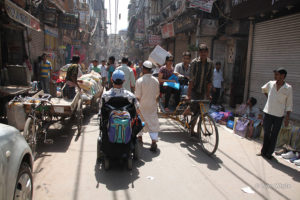 Martin Heng is in a very busy street in India. It shows donkey carts cars and bicycles with street vendors on either side.