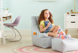 Agirl sits on a bean bag style chair. Next to her is a desk and chair. The chair is designed to rock.