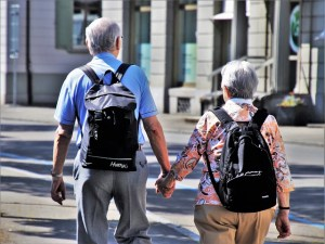 An older man and woman are walking away from the camera down a street. They are wearing backpacks and holding hands.