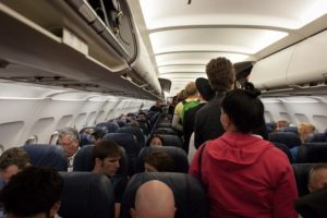 Inside the cabin of an aircraft, people are queuing in the aisle to take their seats