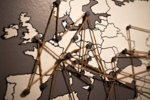 A map of Europe with pins placed in capital cities and string lines linking them together.