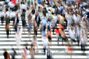 People walking on a wide pedestrian crossing. They are blurred as if they are walking quickly.