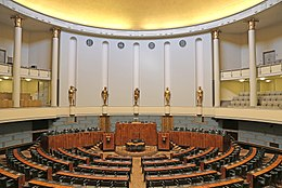 A distant view of a circular seating arrangement in a huge room for the parliamentary members.
