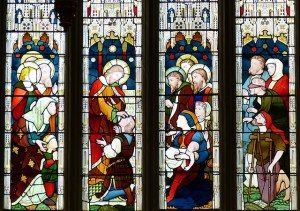 Four panes of a church stained glass window depict different people needing help.