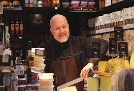 A bald man is standing behind a shop counter that has cheese and other deli items.
