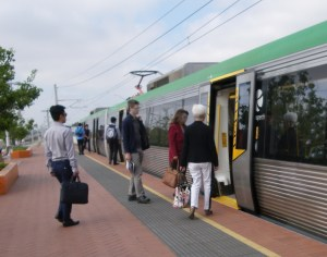 Passengers are getting on a train in Perth. There is a yellow plate that covers the gap between the platform and carriage.