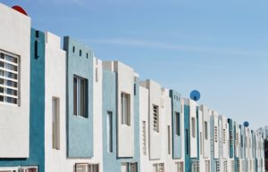 A row of flat front row homes in blue and white.