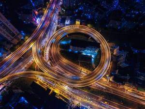 an aerial view of a complex roadway intersection at night where it is lit up with many colours.
