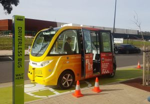 A yellow automated driverless vehicle is parked by the footpath.