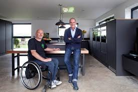 Kevin McCloud stands in the kitchen with Mark Butler who sits in a wheelchair.