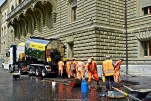 Road workers in hi-vis vests are laying bitumen. Counting costs don't count.