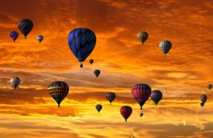 A orange-yellow sky with many coloured hot air balloons.