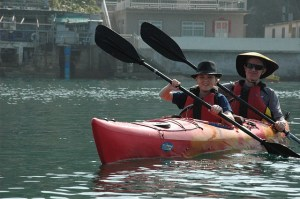 A man and boy are wearing hats and paddling in an orange kayak..