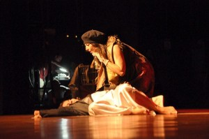 Two women are on stage. One is lying down and looks dead. The other leans over her with grief.