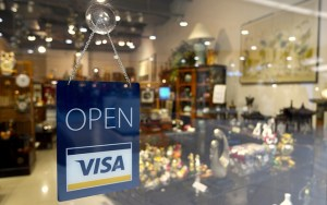 A Visa credit card sign is hanging in the window of an attractive looking shop..