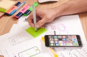 A desk has highlighter pens in different colours, working papers and a smart phone.