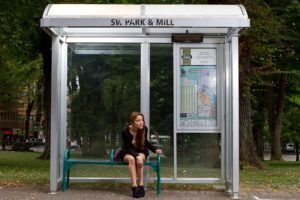 A young woman is sitting in a bus shelter and looking down the road. The shelter is lit and has an information board.