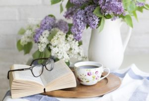 A vase of purple and white flowers sits on a small table with a cup of tea, an open book and a pair of glasses.