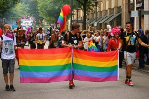 Three young men lead a street march with rainbow banners. It's a gay pride event.