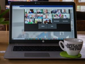 A laptop screen shows several faces of people who are meeting online.