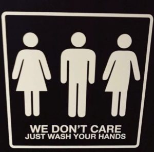 A toilet sign with three icons: one indicating female, one male, and one both. The words are we don't care - just wash your hands.