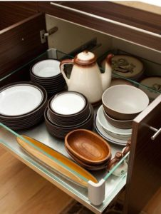An open kitchen drawer showing stored crockery and a coffee pot.